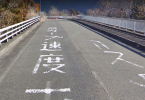 1日2台が横転する事故現場:速度落とせの路面標識
